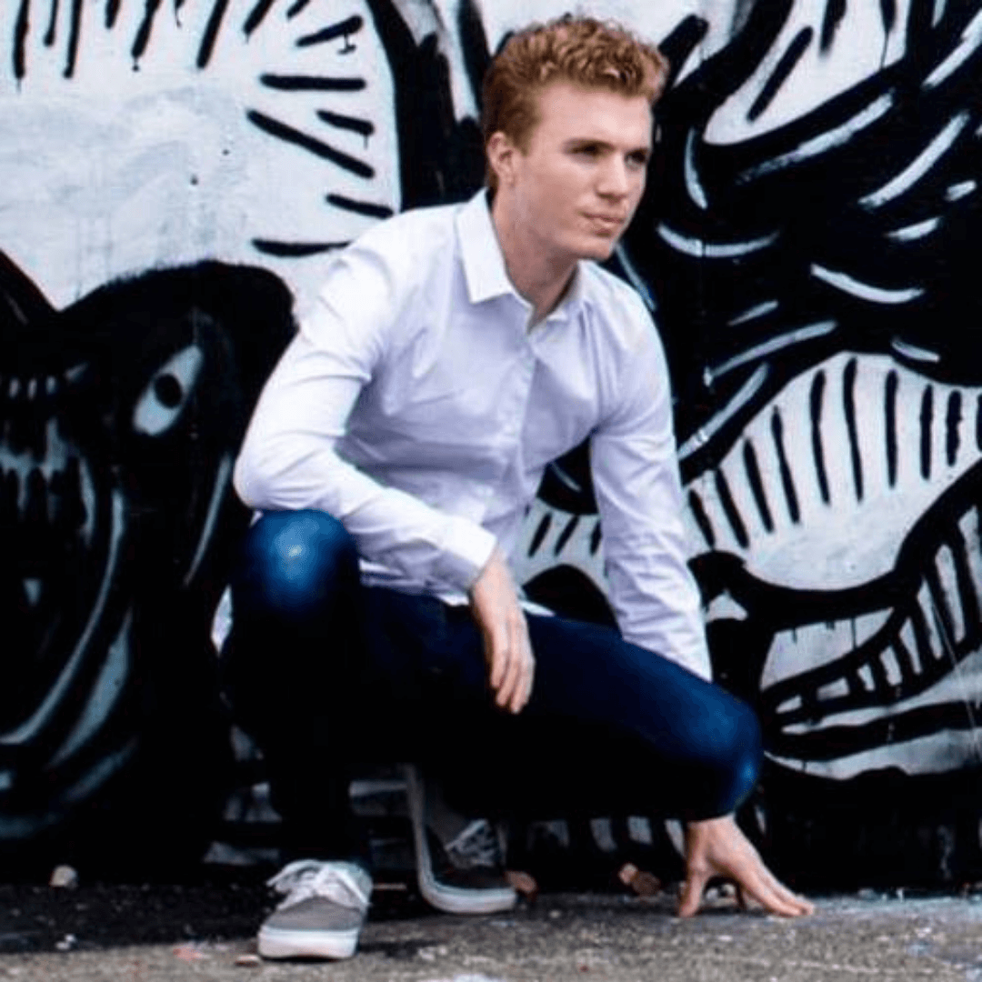 A man sitting in front of graffiti wall
